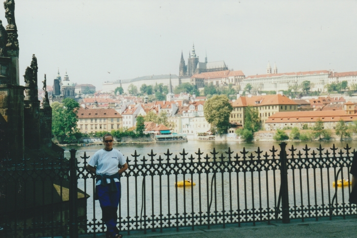 Me standing beside the Charles Bridge with Prague Castle across the river.